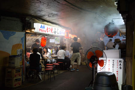 glimpse: Tokyo, Japan - 21 June 2016: The backstreet cafes and bars of Shinbashi. These street cafes are frequented mainly by locals, and are a glimpse of traditional culture away from the tourist trail. Editorial