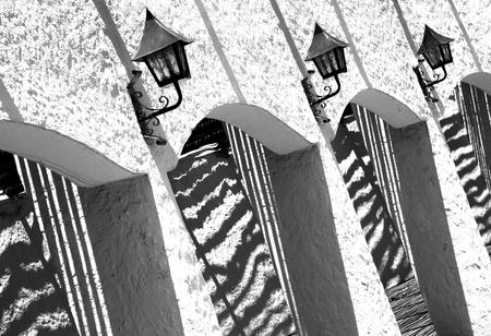 black shadows: Abstract black and white study of shadows and bright sunlight. Exterior wall with lanterns and archways.