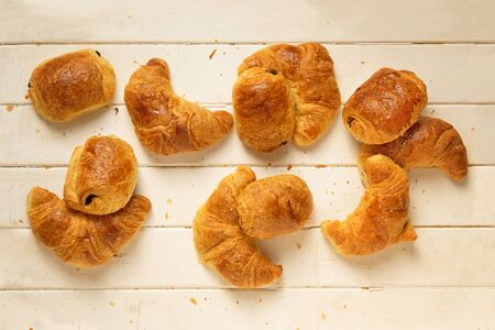 Top view of fresh croissants and pain au chocolat over old wood background.