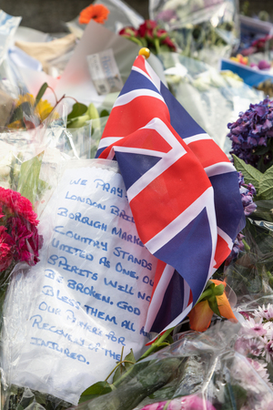 tributos: London, UK - 7 June 2017: Floral tributes and a Union Jack laid as a memorial to the victims of the terrorist attack that to place in Borough Market and London Bridge on 4th June 2017.