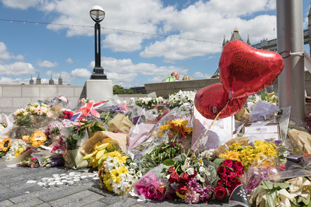 tributos: London, UK - 7 June 2017: Floral tributes laid on the South Bank as a memorial to the victims of the terrorist attack that to place in Borough Market and London Bridge on 4th June 2017. Editorial