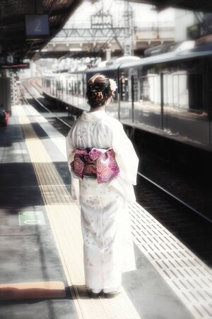 maiko: Retro style depiction of a young Geisha on a train station platform in Japan. Faded, nostalgic style image with the obi toned in bright purple.