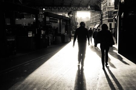 end of a long day: London, UK - 29 Sept 2016: End of the day at Borough Market in Southwark. People make their way out of the market as it closes. Street photography style black and white image capturing the low light and long shadows as the sun sets. Editorial