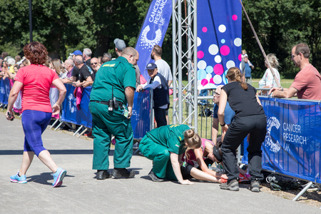 Southampton, Uk - 2 July 2017: Young athlete, suffering from heat exhaustion, is help by paramedics at the finish line of Race for Life. This annual race is run by women to raise money for Cancer Research.