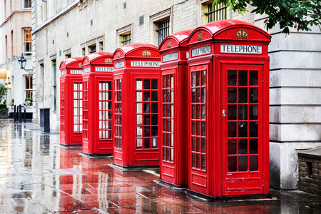 Five British red phone boxes in a row. A line of phone booths in Covent garden after the rain.