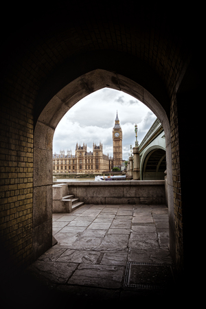 The Houses of Parliament, Big Ben and the Westminster Bridge, framed by a brick archway on the South Bank district of London. Stock Photo