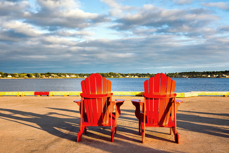 Two red adirondack chairs on the quayside at Charlottetown, Prince Edwad Island, Canada Stock Photo