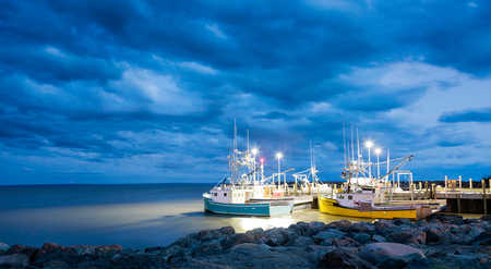 Fishing boats moored in Alma, Bay of Fundy, on the New Bruswick Atlantic coastline in Canada. Blue hour shot with dramatic clouds.