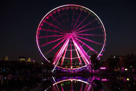 Illuminated ferris wheel in the Old Port of downtown Montreal. Long exposure night scene with motion blur to the wheel and reflection, with the modern architecture of the city of Montreal in the background.  Archivio Fotografico