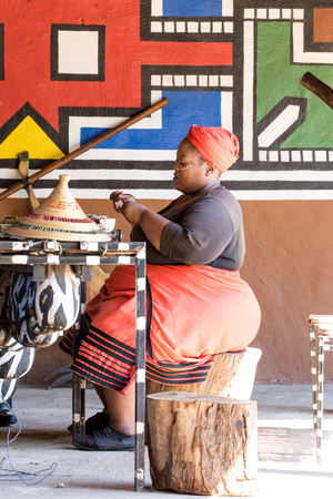 Lesedi Cultural Village, South Africa - 4 November 2016: African woman engaged in craftwork to produe traditional souvenirs for tourists.
