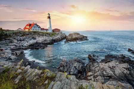 Porland Head Lighthouse at dusk, and the rugged coast of Portland, Maine.