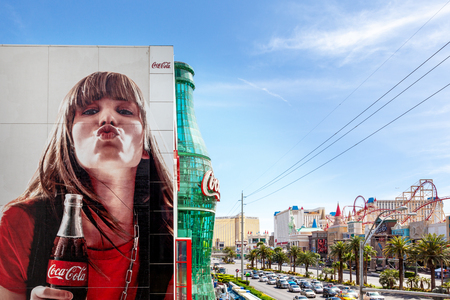 Las Vegas, USA - 18 April 2012:  Advertising billboard and giant glass Coke bottle of he Coca Cola store on the Las Vegas strip, with the hotel casinos of New York, Excalibur and Mandalay Bay beyond..