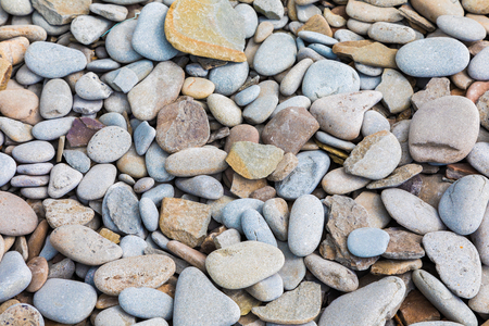 Beach pebble background in various shades of greys, blues, reds and browns.