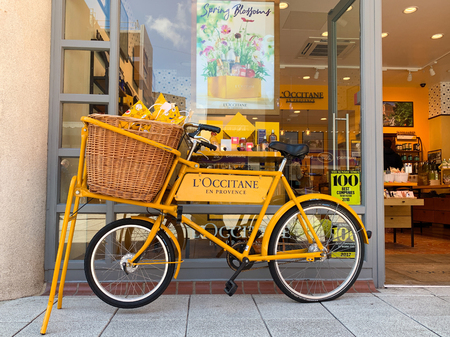 Portsmouth, UK - 10th May 2019: Yellow bike, advertising L Occitane En Provence, outside their store in Gunwharf Quays, Portsmouth UK. This company is committed to natural and cruelty free products.