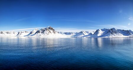 Blue sky, blue and snowy mountains in the beautiful fjords of Svalbard, a Norwegian archipelago between mainland Norway and the North Pole