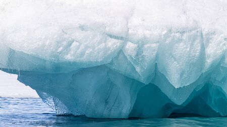 Glacial blue ice background with space for your text. Underside of a snow covered iceberg in Svalbard, a Norwegian archipelago between mainland Norway and the North Pole