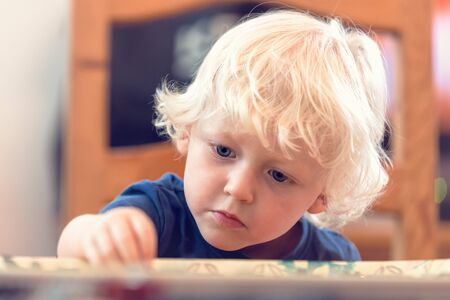 Small blond boy playing at the table and concentrating on his game.