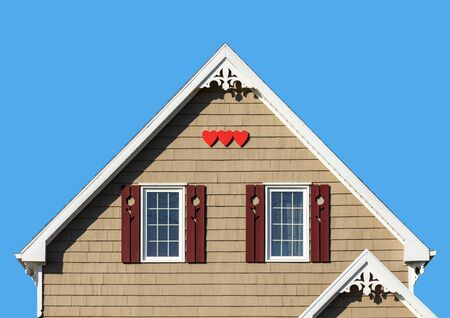 Detail of the gingerbread style fretwork of the typical wooden houses of Iles de la Madeleine, or the Magdalen Islands, in Canada. Hearts and wooden shutter details Reklamní fotografie