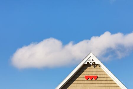 Detail of the gingerbread style fretwork of the typical wooden houses of Iles de la Madeleine, or the Magdalen Islands, in Canada. Hearts and single puffy cloud in a blue sky.