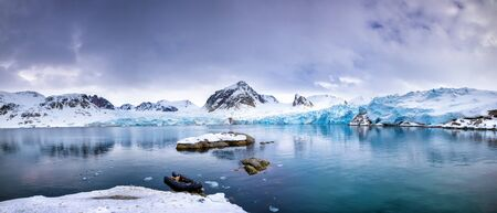Panarama of the mountains, snow and blue glacial ice of the Smeerenburg glacier, Svalbard, and archipelago between mainland Norway and the North Pole. An inflatable boat is anchored in the foreground. Reklamní fotografie