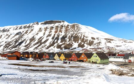 Row of colourful chalet houses in Longyearbyen, Svalbard. Blue sky and mountain background with snowmobiles parked in the foreground.