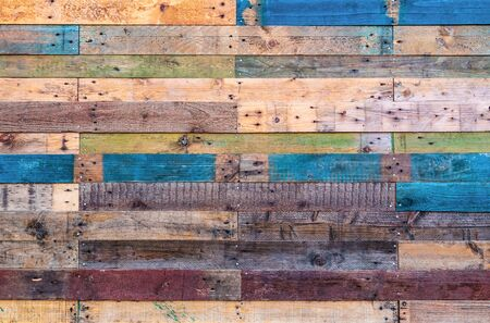 Grunge wood background in natural shades with red, green and blue. Rustic style rough planks with nails, holes and a variety of shades and textures.