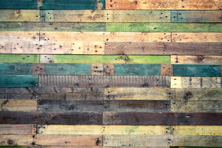 Grunge wood background in natural shades with green and blue. Rustic style rough planks with nails, holes and a variety of shades and textures.
