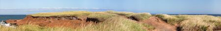 Panorama of the rugged coastline of the Magdalen Islands, or Les Iles de la Madeleine, Canada. Photostitch showinng the red cliffs, windswept grass and cold blue water of the Gulf of Saint Lawrence. 版權商用圖片 - 134871707