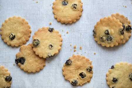 Flatlay of blueberry shortbread with crumbs, on a linen tablecloth.