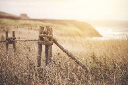 A rustic clifftop fence in Harve Aubert, Magdalen Islands, Canada. Matte processing vintage effect.