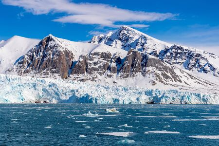Blue sky, blue glacier and snowy mountains in the ice floes and fjords of Svalbard, a Norwegian archipelago between mainland Norway and the North Pole