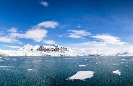 Panorama des blauen Himmels, des blauen Gletschers und der schneebedeckten Berge und der Eisschollen und Fjorde von Spitzbergen, einem norwegischen Archipel zwischen dem norwegischen Festland und dem Nordpol Standard-Bild