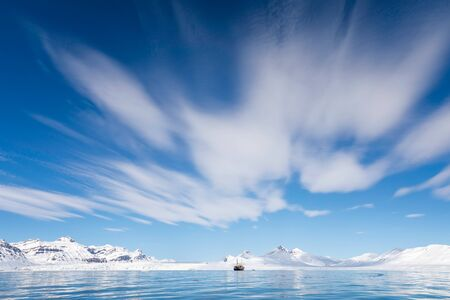 Boat on the fjords of Svalbard, a Norwegian archipelago between mainland Norway and the North Pole, with snowy mountains and vast blue sky background. 스톡 콘텐츠