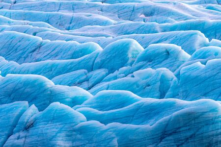 Sunlight catches the edges of blue glacial ice at the Svinafellsjokul glacier in southeast Iceland. This is the largest ice cap in Europe.
