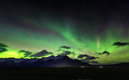 The snow covered mountains of Iceland with the Aurora Borealis, or Northern Lights, ligtting up the night sky.