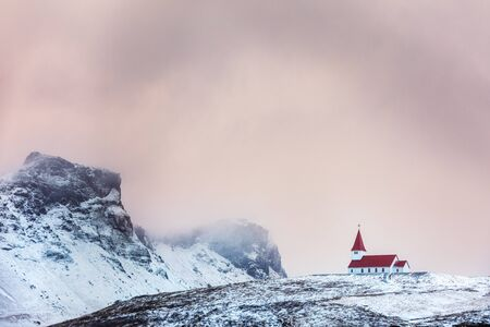 Vik i Myrdal church, in Vik, Iceland, against snowy mountain background and pink sky at dusk. This picturequese, red roofed  Church is perched on a hilltop above the village.