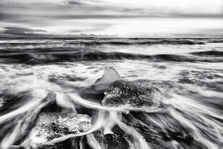 Sunrise on Diamond Beach, Iceland. The black volcanic sands are littered with chucks of glacial ice that have broken from the nearly glacier lagoon and drifted out towards the sea. Black and white.