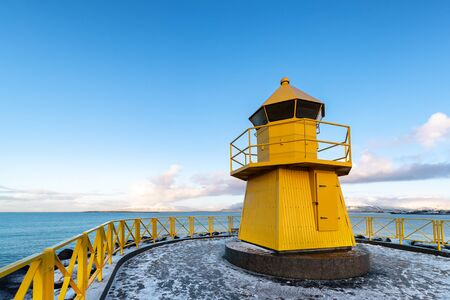 Small yellow lighthouse on the coast of Reykjavik, Iceland. The sea, blue sky and snow covered mountains can be seen in the background.  스톡 콘텐츠