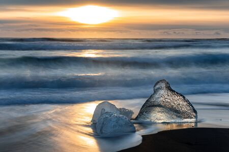 Sunrise on Diamond Beach, Iceland. The black volcanic sands are littered with chucks of glacial ice that have broken from the nearly glacier lagoon and drifted out towards the sea.  스톡 콘텐츠