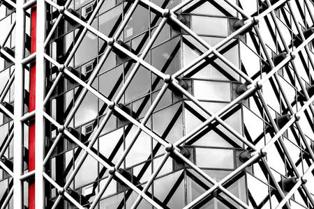 Architectural abstract. Generic modern building exterior in black and white with a touch of red. Horizontal tubular framework over glass. 免版税图像