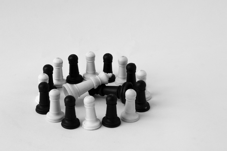 Pawns stand around in front of the fallen kings