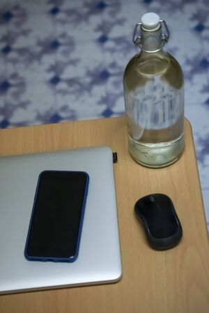a glass bottle filled with water along with laptop and mobile on a table