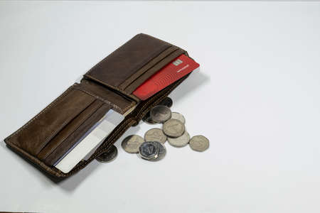 a wallet and UAE dirhams and coins with white background