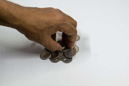 A man hand taking UAE currency coins with white background, fils,