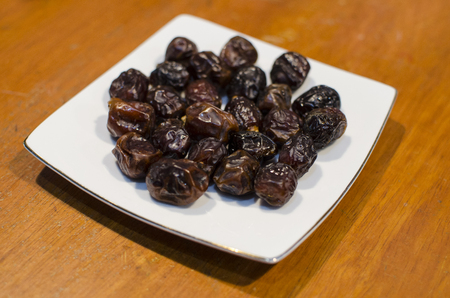 Date fruits on the white wooden table