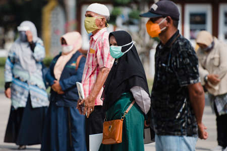 Visitors wear masks and stand far apart to prevent the transmission of the COVID-19 outbreak while visiting the Banda Aceh City government office, Aceh province, Indonesia. Tuesday, March 21, 2020.