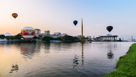 adventure aeronautical: 7th Putrajaya International Hot Air Balloon Fiesta with 3 hot balloons on the air reflection on the lake with colorful morning skies Editorial