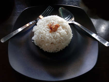 rice plate: White rice on the black plate with spoon and fork