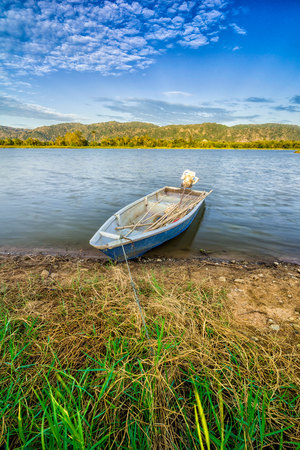 This fisherman boat park at the lake side with a background of the beautiful mountain and blue sky Stock Photo