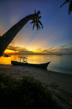 Ray of golden light between coconut trees framing in Gertak Sanggul, Pulau Pinang beach during sunrise Stock Photo